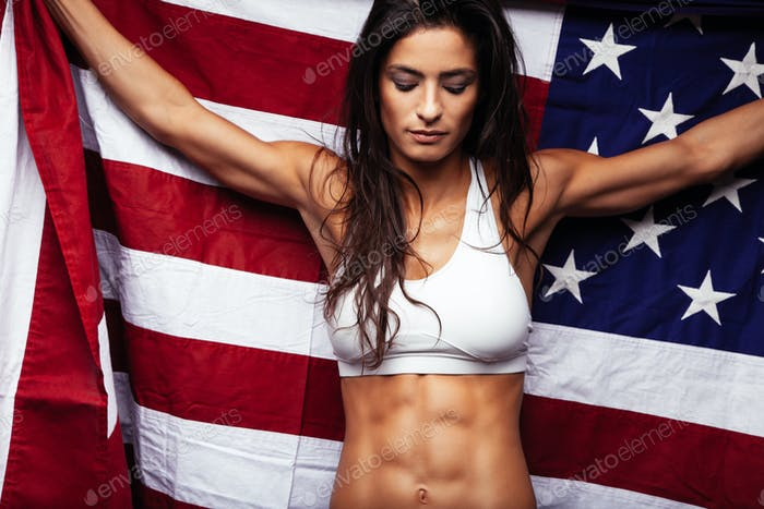 Female athlete holding country flag proudly