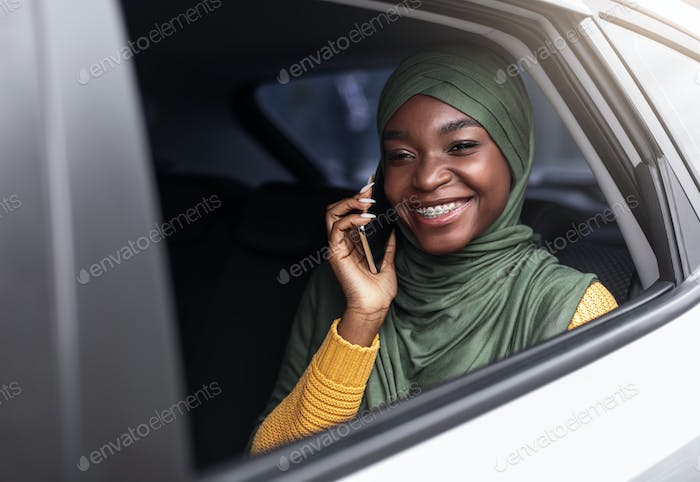 Black muslim lady travelling by car on backseat and talking on cellphone