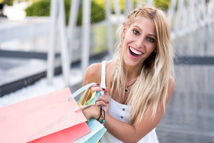 Blonde happy young woman shooping with bags outdoors
