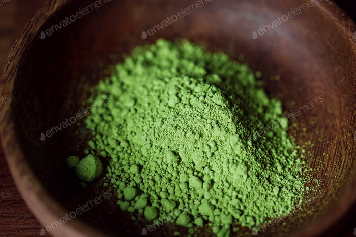 Macro photography of matcha green tea powder in a wooden bowl.