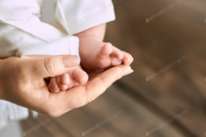 Female hand holding baby feet
