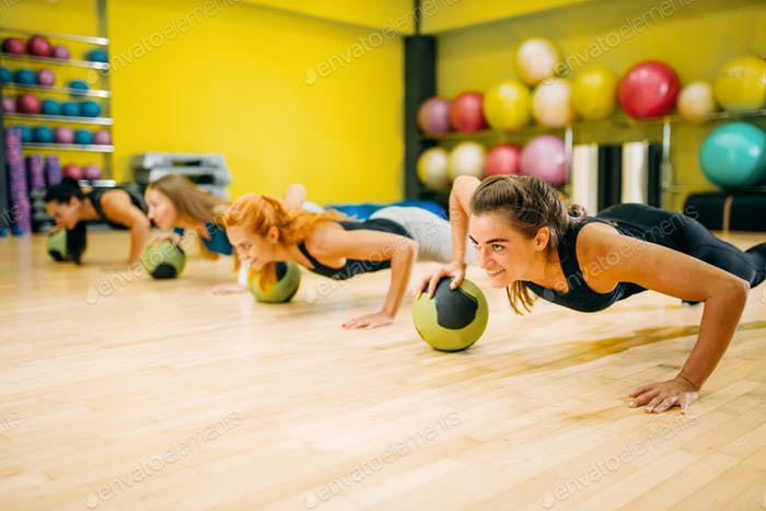 Women group with balls doing push up exercise