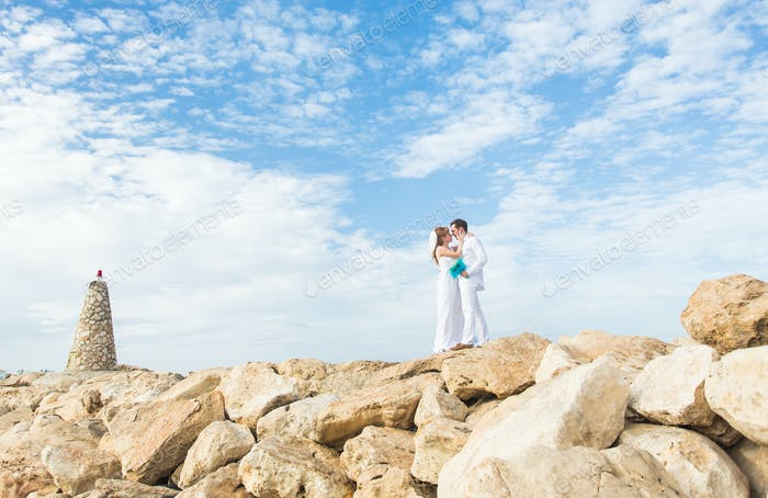 Wedding couple standing on the cliff. Groom tenderly embraces the bride.