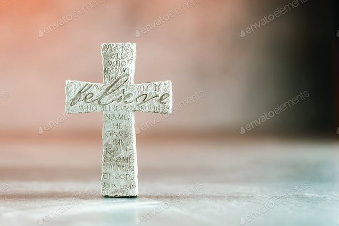 Stone cross with inscription Believe on grey background, Copy space. Christian backdrop. Biblical