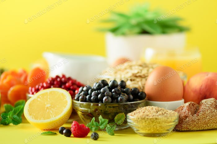Breakfast served with soft boiled egg, oat flakes, nuts, fruits, berries, milk, yogurt, orange