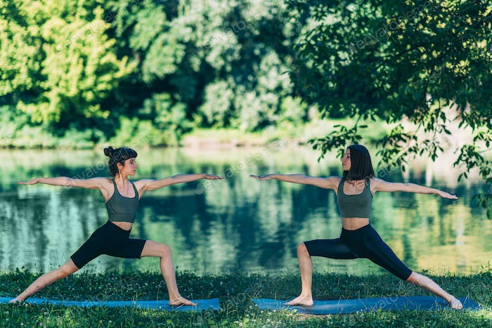 Yoga Women by The Lake. Warrior Pose