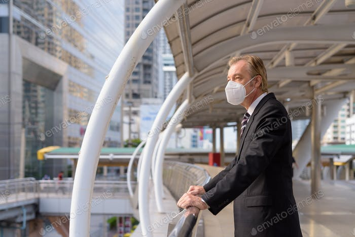 Mature businessman with mask thinking and looking at view of the city