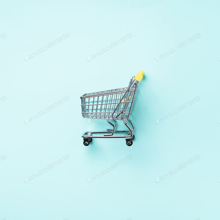Shopping cart on blue background. Minimalism style. Square crop. Creative design. Top view with copy
