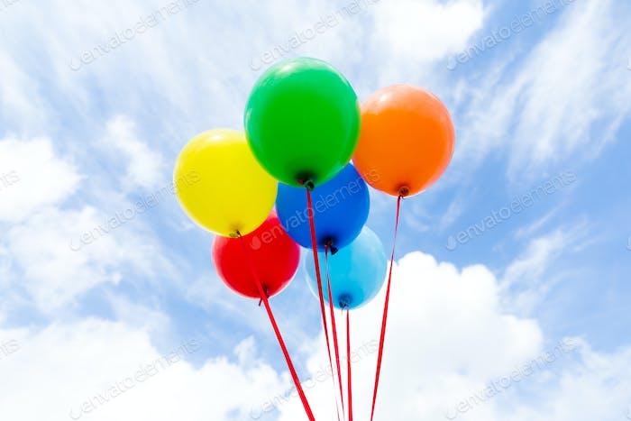 Eine Gruppe von bunten Ballons mit blauem Himmel Hintergrund