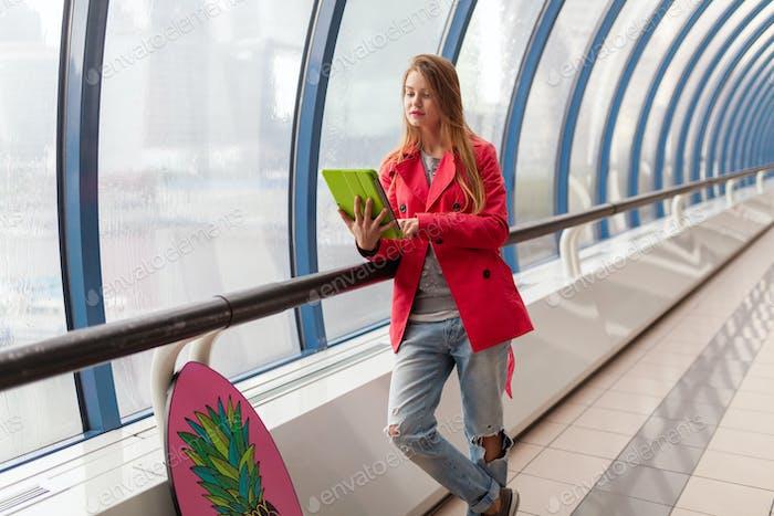 Junge hübsche Frau im lässigen Outfit mit Tablet-Lap