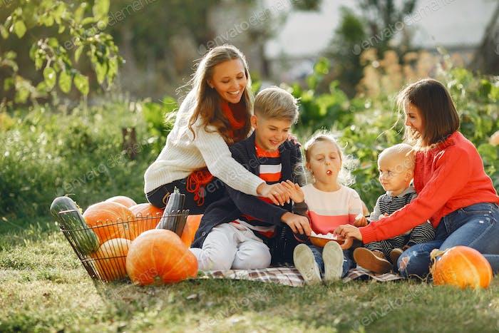 Big family sitting on a garden near many pumpkins