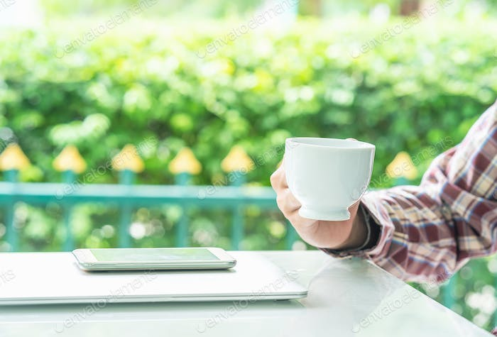 Male hand holding smart phone and cup of coffee_-2