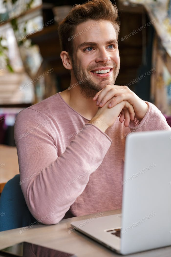 Handsome young man working on laptop computer