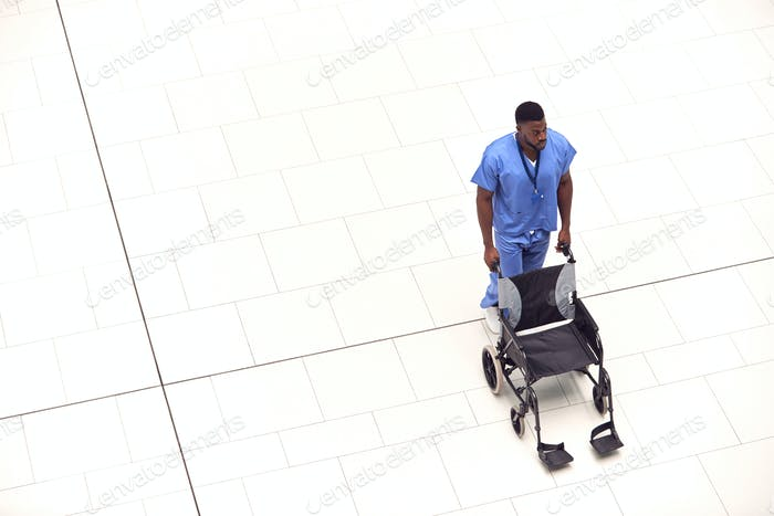 Overhead View Of Male Nurse Pushing Empty Wheelchair Through Lobby Of Modern Hospital Building