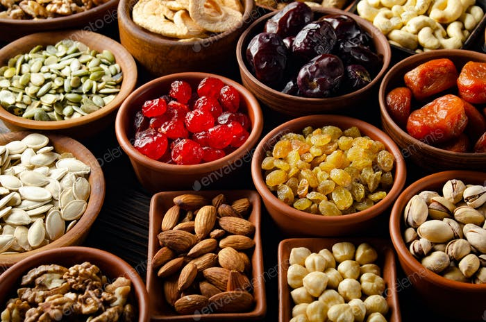 Assorted nuts seeds and dehydrated fruits in bowls on wooden kitchen table