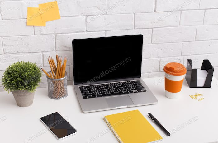 Orange style workplace with laptop on white office table