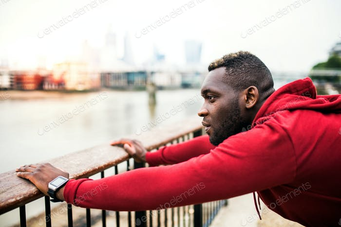 Young sporty black man runner on the bridge outside in a city, stretching.