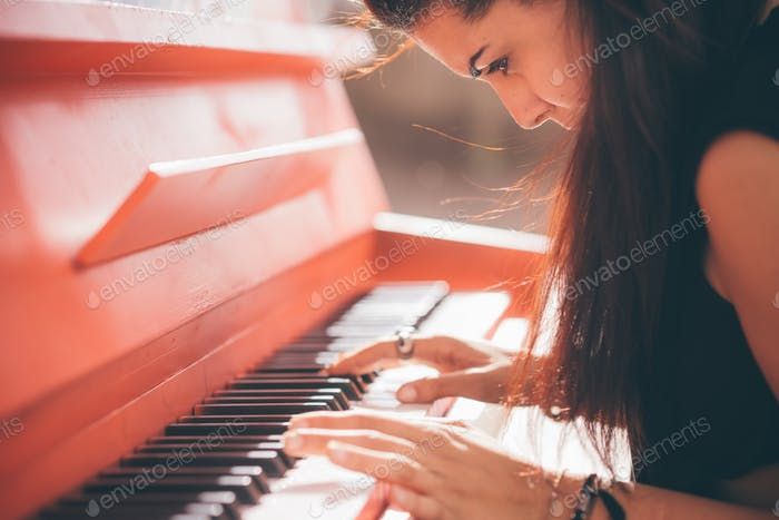 Young beautiful caucasian girl playing piano