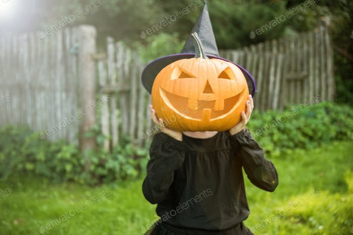 Funny girl with halloween pumpki in garden