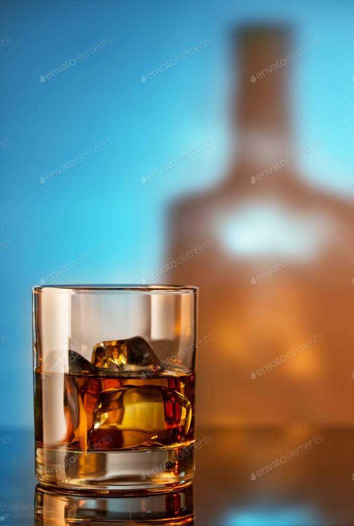 Glass of whiskey with ice against the background of the bottle
