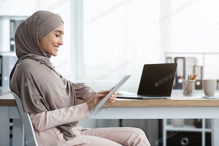 Lächelnd islamische Geschäftsfrau mit digitalen Tablet während Sitzen am Arbeitsplatz