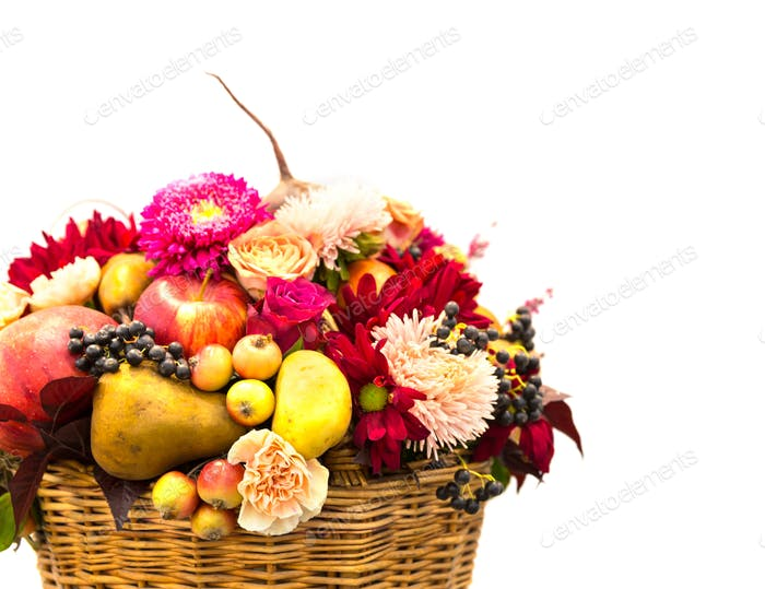 Ripe fruits and flowers composition in a basket