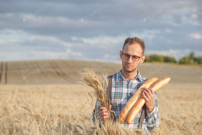 Happy farmer hold bakery products and ears of corn standing in ripe wheat field