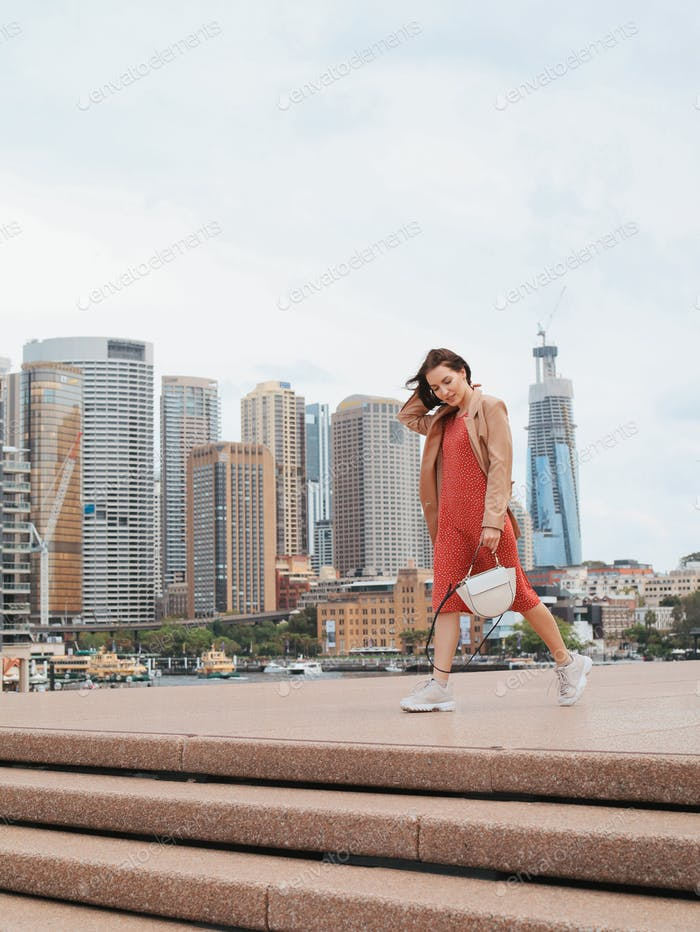 Woman in a red dress walks the streets of Australia