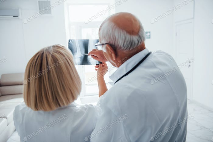 Senior man and woman doctors in white uniform examines x-ray of human legs
