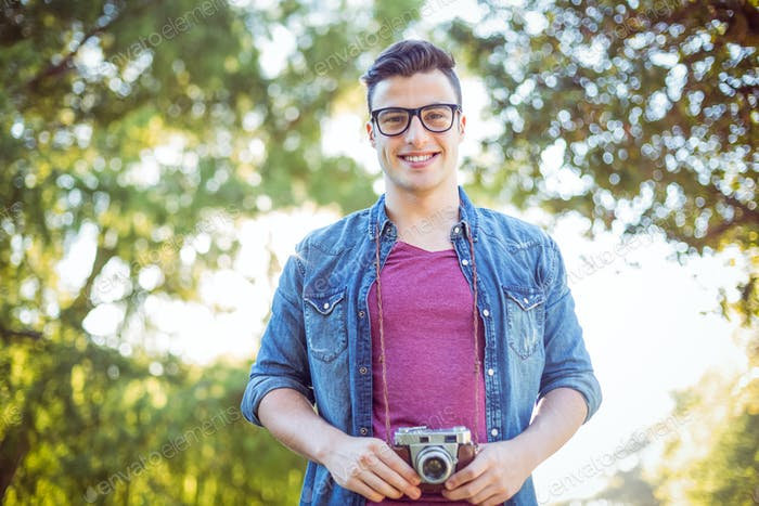 Handsome hipster holding vintage camera on a sunny day