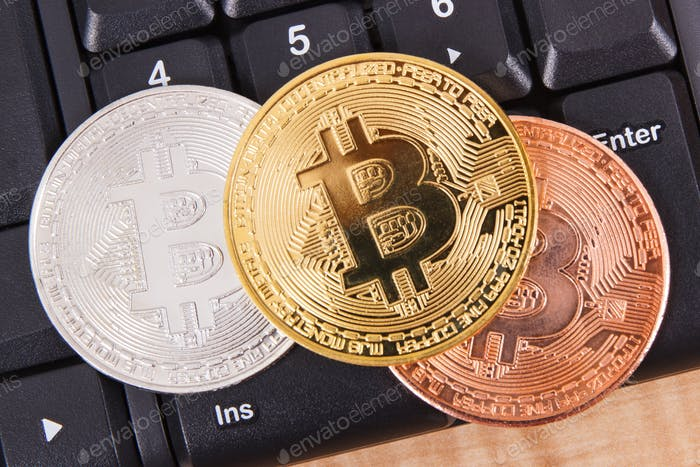 Bitcoins on computer keyboard, symbol of electronic virtual money and mining cryptocurrency concept