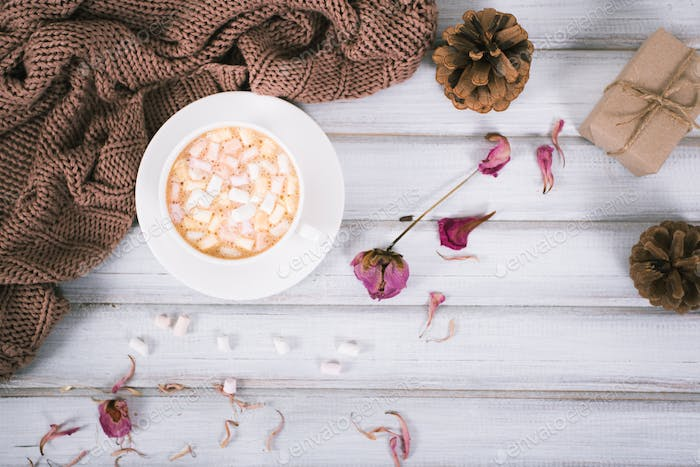 Winter coffee in a ceramic cup with marshmallow, warm scarf