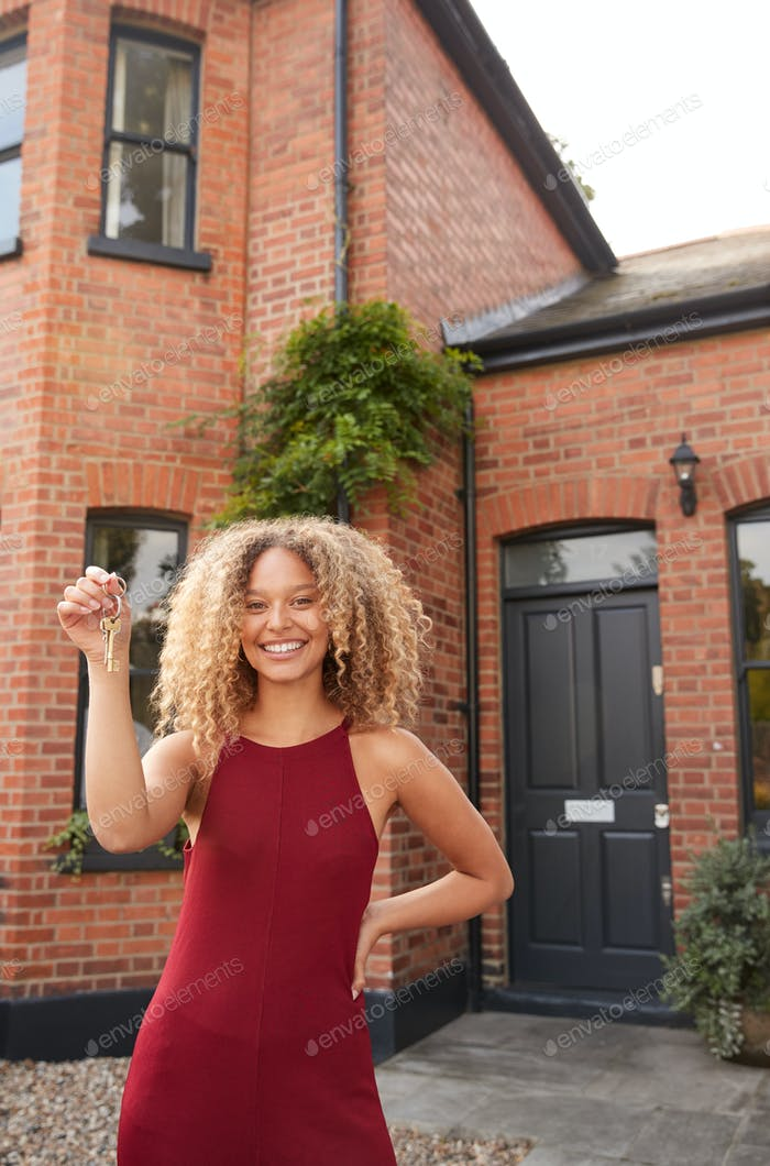 Portrait Of Excited Young Woman Standing Outside New Home Holding Keys