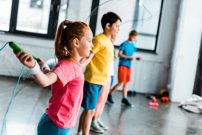 Preteen kids training with skipping ropes in gym