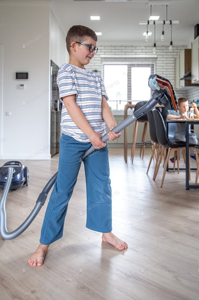 Funny little boy with a vacuum cleaner cleans houses.