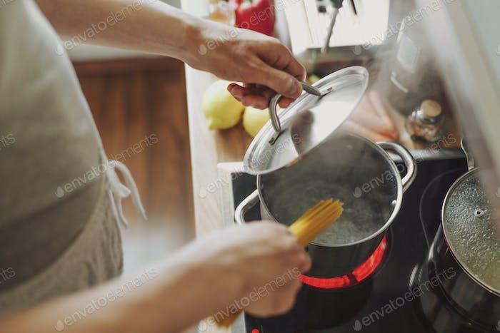 Hombre cocinar pasta en la cocina