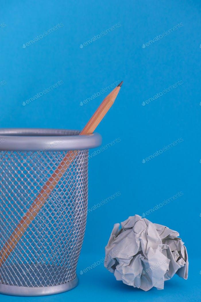 Bleistift in Mülleimer mit zerknitterten Papierkugel in der Nähe