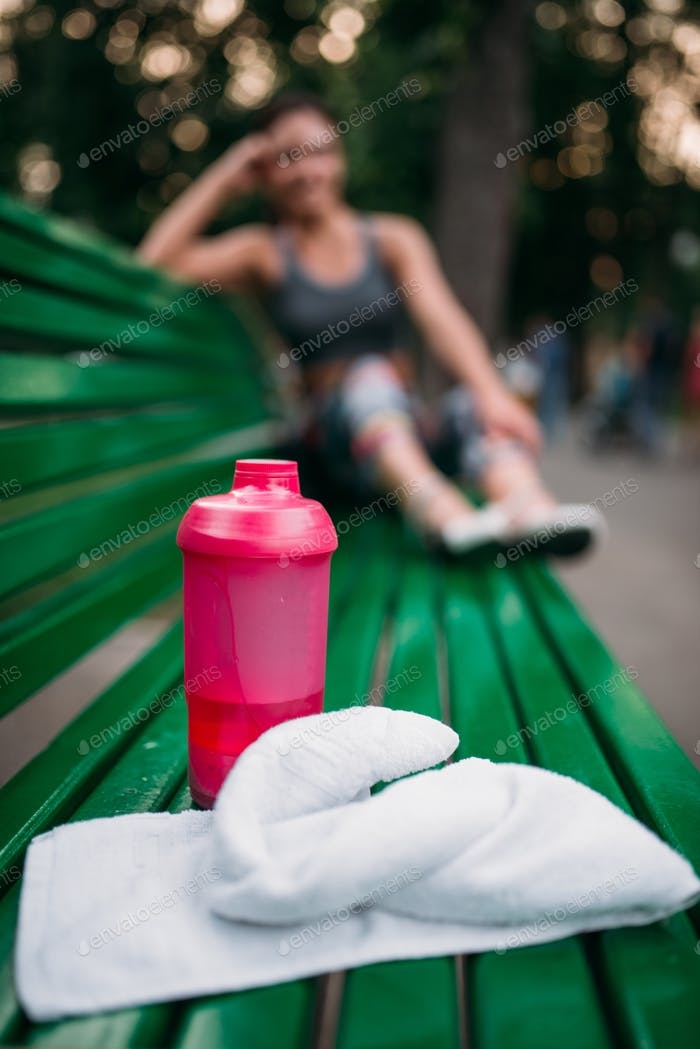Sport bottle and towel on a bench in summer park