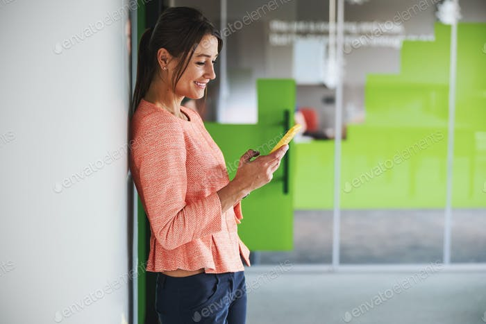 Young smiling female consultant in pink jacket reading something on smartphone in the meeting room