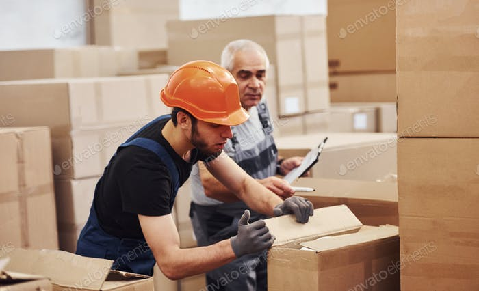 Young and senior storage workers in uniform works together in the warehouse