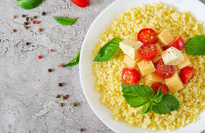 Millet porridge with cheese, butter and basil in white bowl.