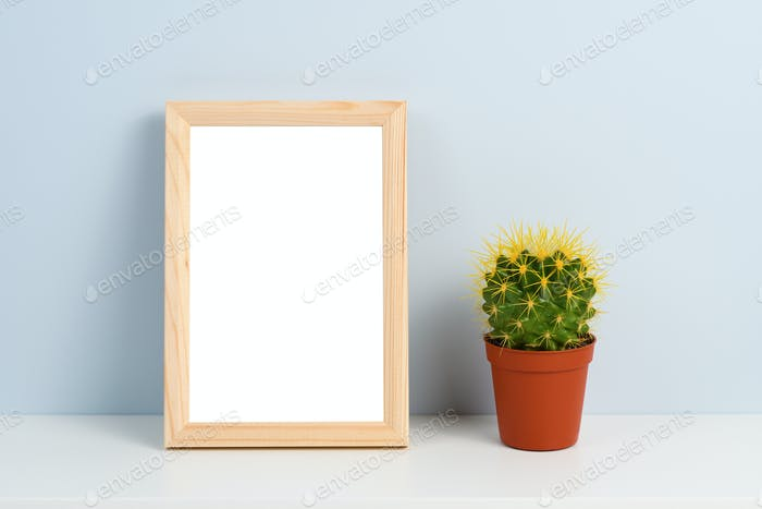 Cactus in pot and wooden photo frame on shelf