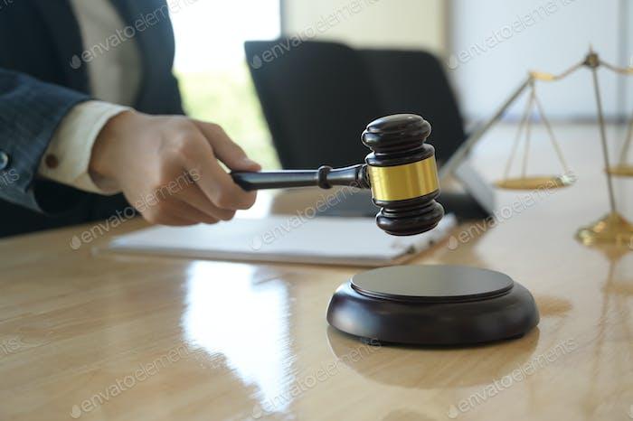 Konzept der Gerechtigkeit, Anwalt hält einen Hammer vorgibt, auf einem Holztablett auf dem Schreibtisch zu schlagen.