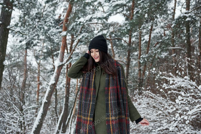 Holidays season. Cheerful young girl in warm clothes have a walk in the winter forest at daytime