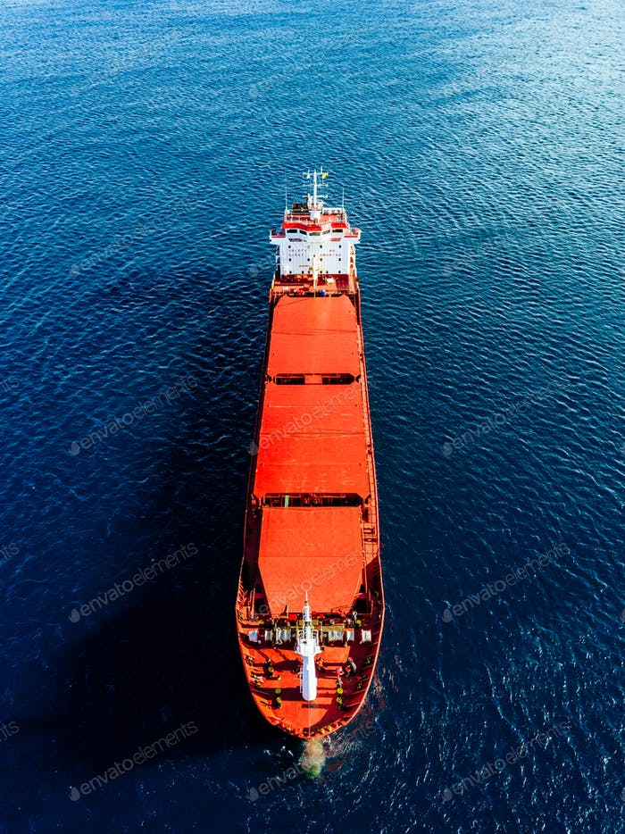 Aerial view of general cargo ship in blue sea. View from above