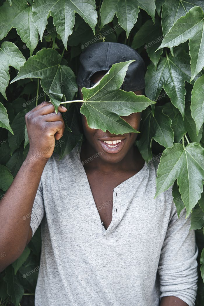 divertido afroamericano hombre sosteniendo una hoja verde