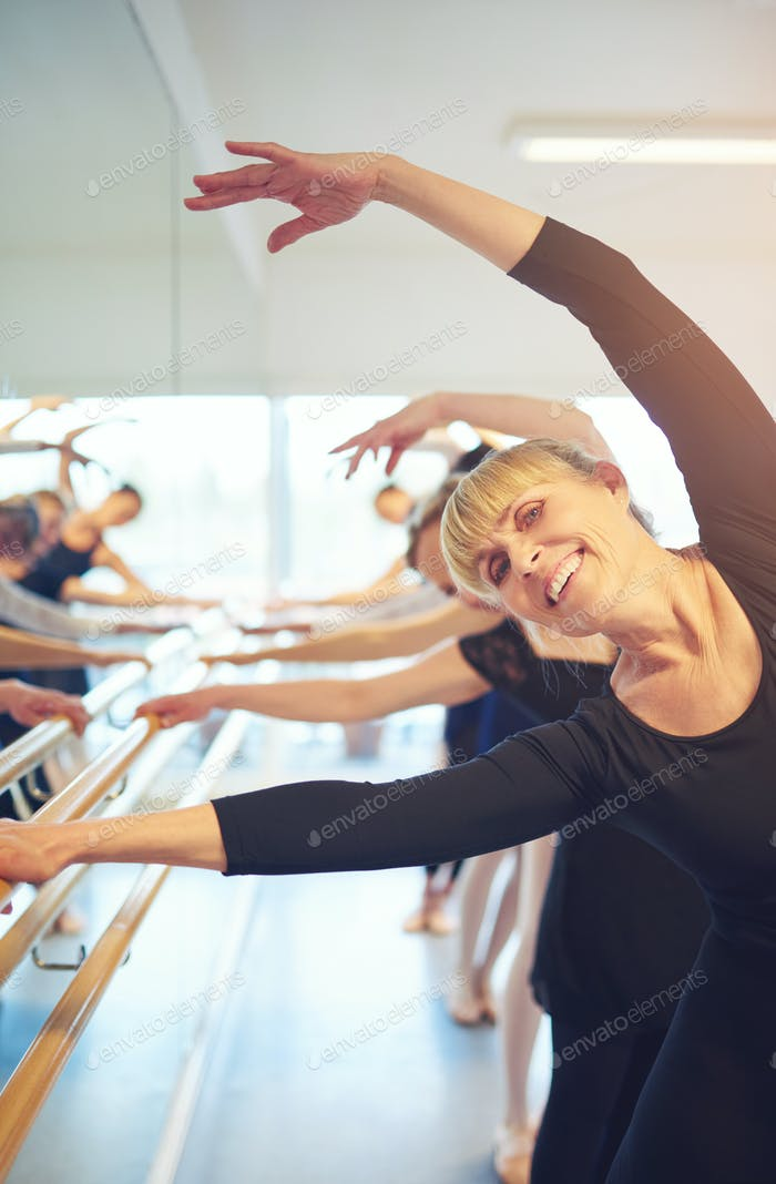 Smiling adult woman stretching and doing gymnastics in ballet class