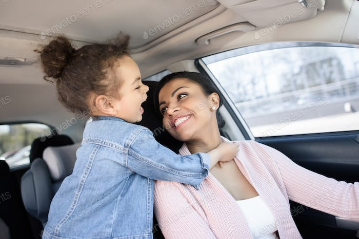 little african american girl with mother sitting in car
