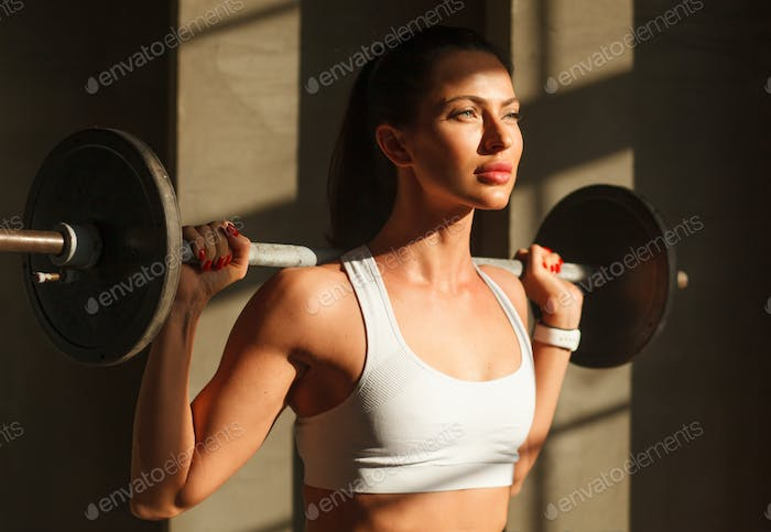 attractive hispanic sportswear with barbell on shoulders