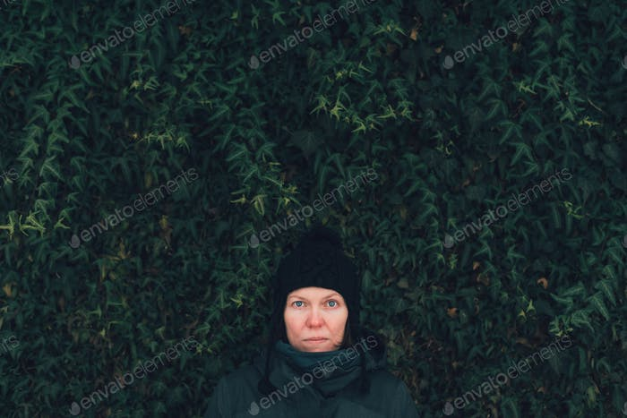 Serious woman in winter clothing against the ivy wall